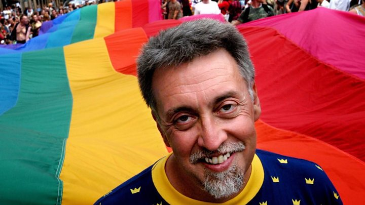 Gilbert Baker, 2 de junio de 1951— 31 de marzo de 2017, con la bandera arcoiris de fondo